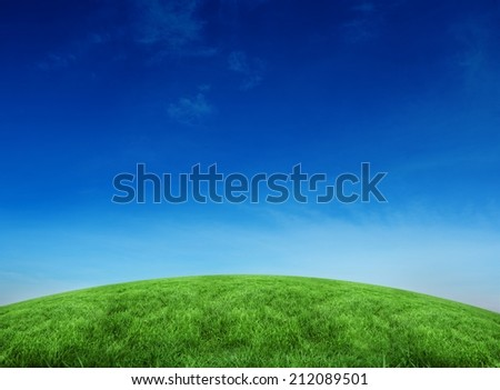 Green hill under blue sky with large copy space - stock photo