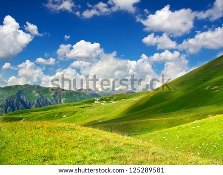 Green hills in mountain valley and cloudy sky. Summer landscape - stock photo