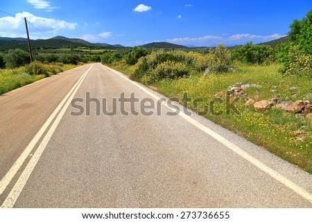 Green hills of Attica near straight road under blazing sun, Greece - stock photo