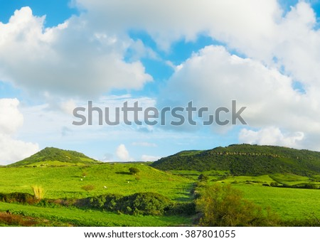 green hills under a blue sky with clouds in Sardinia, Italy - stock photo