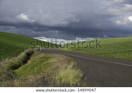 Green hills with road going through. Dark rain clouds coming. - stock photo