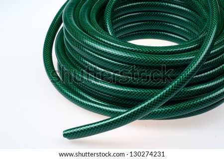 Green hose pipe on white background- selective focus on the front - stock photo