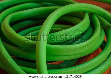 Green hose reel on tile. - stock photo