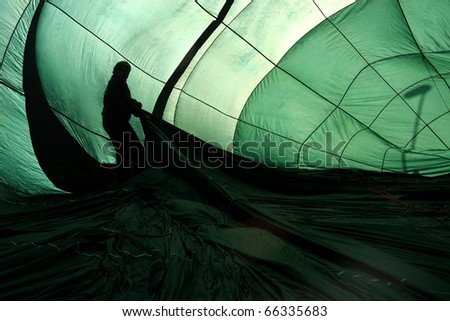 Green hot air balloon being inflated with silhouette of pilot in the interior - stock photo