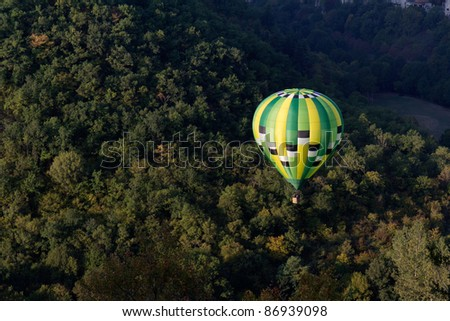 Green hot air balloon flying near Rocamadour. - stock photo