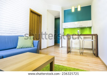 Green hotel room with sofa and kitchenette - stock photo
