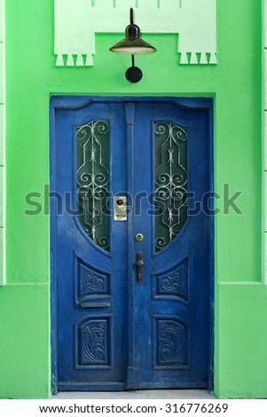 Green House Wall Fragment With Retro Blue Wooden Door And Old Hanging Lamp, Carved Door Have Intercom System And Window With Lattice - stock photo