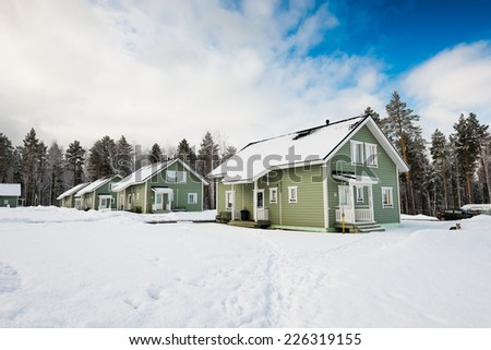 Green houses in snow fairy forest. - stock photo