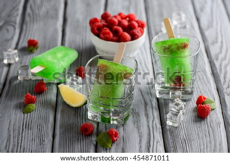 Green Ice Cream Popsicle with Lime and raspberry on a wooden table - stock photo