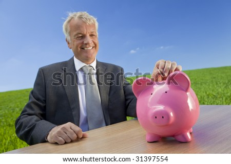 Green investment concept shot of a middle aged man putting a coin into a pink piggy bank in a field with a bright blue sky. Shot on location with the focus on the piggy bank in the foreground.