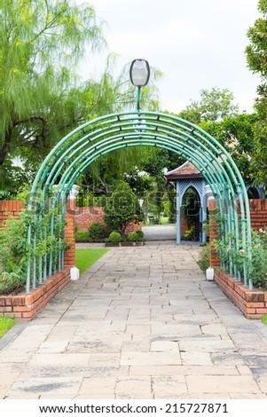 green iron tunnel entry formal garden - stock photo