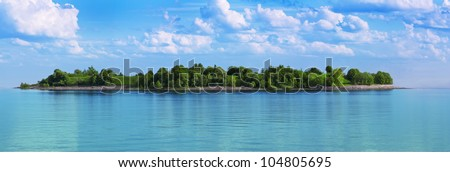 green island in a sea of turquoise water - stock photo