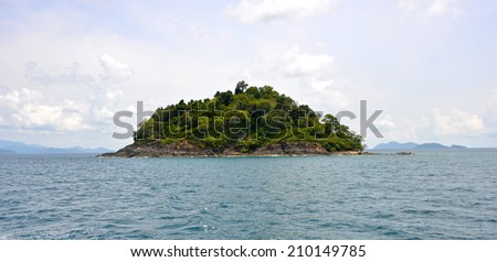 Green island is surrounded with blue sea. This is a lush tropical island (Thailand). - stock photo
