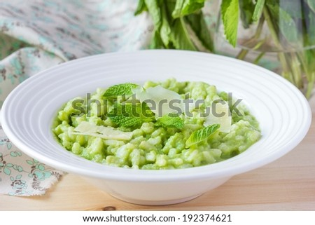 Green Italian risotto with peas, mint, crispy bacon, delicious gourmet dish - stock photo
