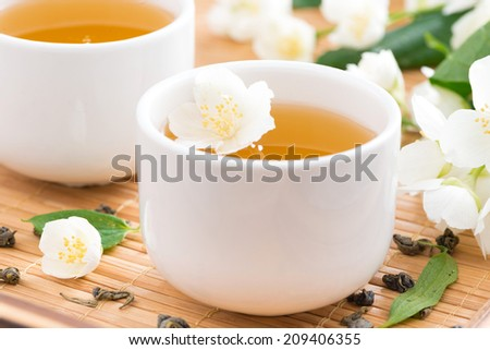 Green jasmine tea in white cups, selective focus, close-up - stock photo