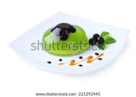 Green jelly with blackcurrant berries and sauce, isolated on white - stock photo