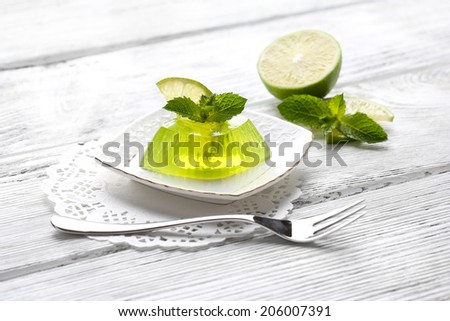 Green jelly with mint leaves on wooden background