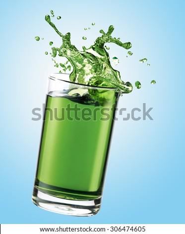 Green juice splashing from glass - stock photo