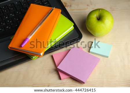 green juicy Apple near the laptop and notebooks and colored with stickers on brown wooden table - stock photo