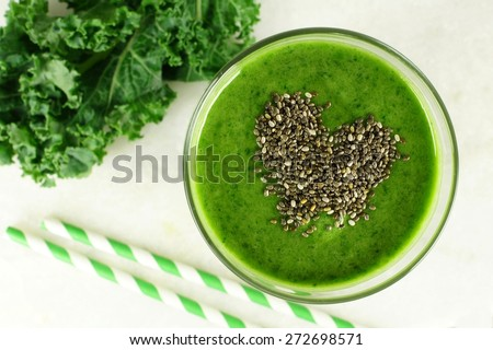 Green kale smoothie downward view in glass with heart shape made of healthy chia seeds - stock photo