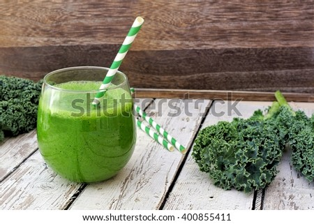 Green kale smoothie in a glass tumbler with straw on a rustic wood background - stock photo