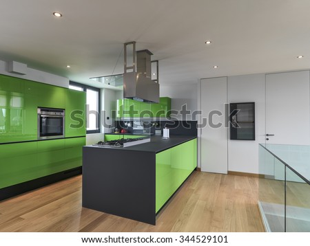 green kitchen with kitchen island in the attic room with wood floor - stock photo