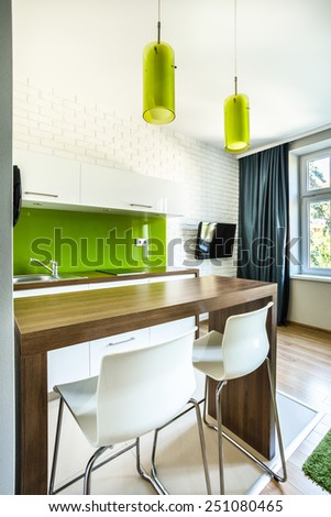 Green kitchenette and dining space in hotel room - stock photo