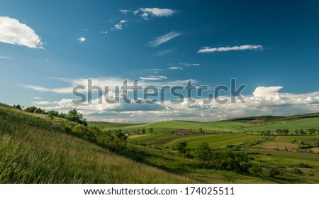 Green landscape. Green field against blue sky - stock photo