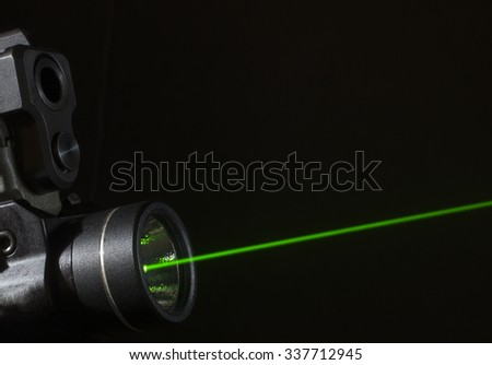 Green laser that is mounted on the bottom of a handgun - stock photo