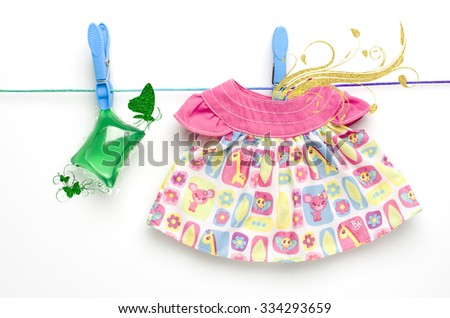 Green laundry gel capsule and dress hanging on washing line on white background. Butterfly spring branch showing fresh smell of washing. - stock photo