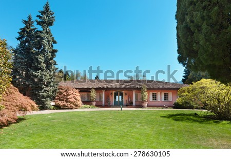 Green lawn and beautiful house in a sunny spring day - stock photo