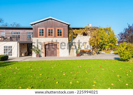Green lawn and traditional house in Tomaszowice village park on sunny autumn day, Poland - stock photo