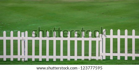 Green lawn and white wood fence