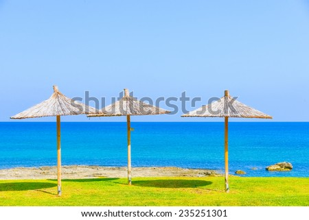 green lawn parasol of straw on a background of blue sea and sunny sky - stock photo