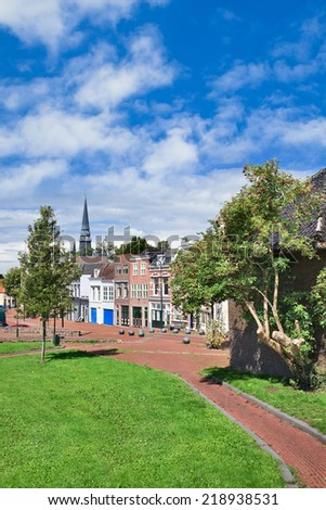 Green lawn with a paved path and row of renovated houses on the background, Gouda, The Netherlands - stock photo