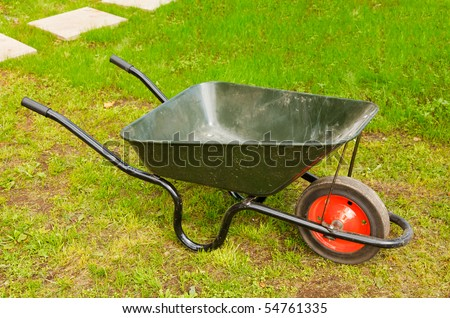 Green lawn with wheelbarrow - stock photo