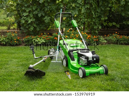 Green lawnmower, weed trimmer, rake and secateurs in the garden. - stock photo