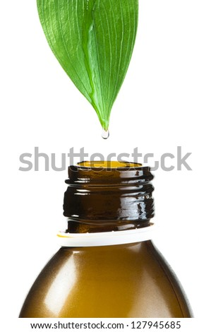 Green leaf and drop over a tube of cosmetics. White isolated - stock photo