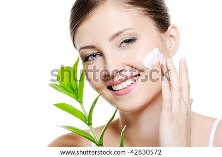 Green leaf near beauty woman  applying moisturiser cream on her clean skin of face - stock photo