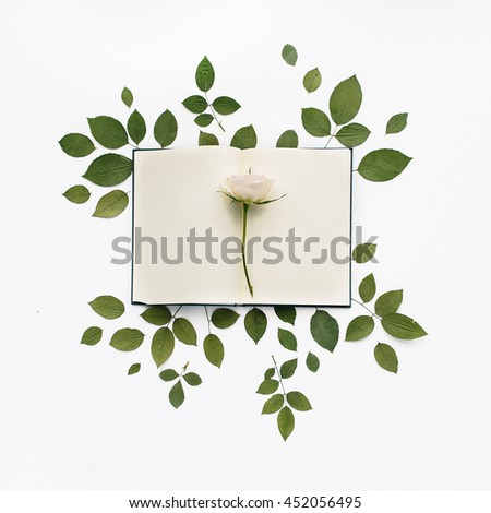 Green leaves and empty notebook isolated on white background. Flat lay, top view - stock photo