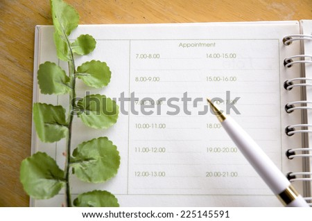 green leaves on appointment book - stock photo