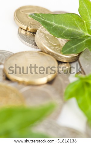 Green leaves placed on various types of coins. - stock photo