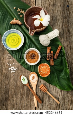 Green leaves with nature spa ingredients turmeric,herbal compress ball,dried indian bael ,cinnamon powder ,cinnamon sticks ,aromatic oil ,star anise and sea salt on rustic background. - stock photo
