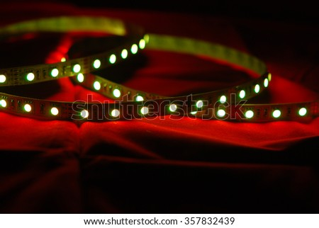 Green led strip on the background of red textile