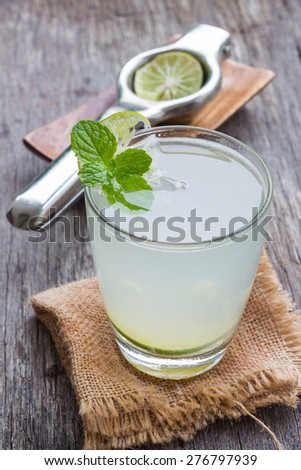 Green lemon juice on wooden background, rustic style