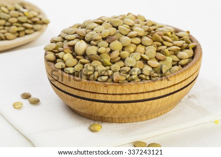 Green lentil seeds in wooden bowl on white background - stock photo