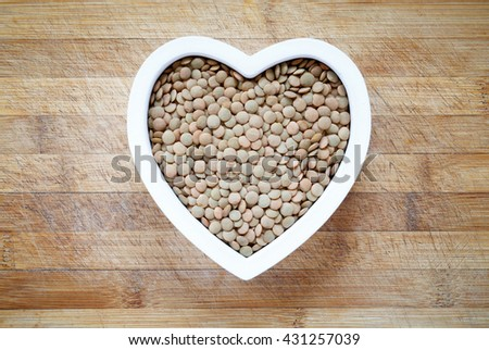 Green lentils in heart shape bowl