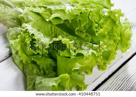 Green lettuce leaves. Lettuce leaves on wooden background. Fresh lettuce on kitchen table. Healthy organic food. - stock photo