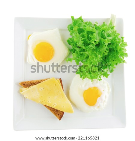 green lettuce salad and fried eggs on white - stock photo