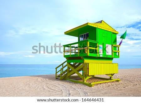 Green lifeguard house in South Beach, Miami Beach Florida on late summer afternoon with ocean in the background - stock photo